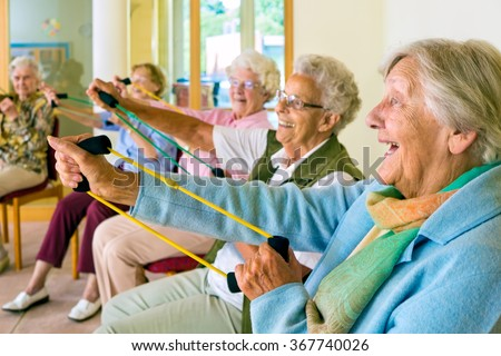 Large group of happy enthusiastic elderly ladies exercising in a gym sitting in chairs doing stretching exercises with rubber bands - stock photo