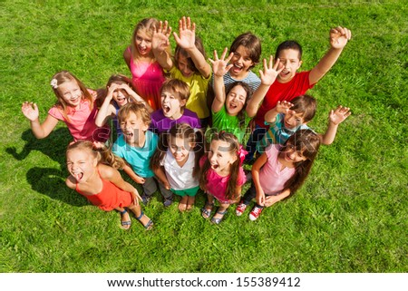 Large group of happy kids, boys and girls, about 10 years old standing on the green grass top view - stock photo