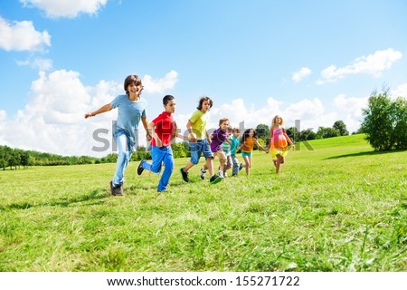 Large group of happy kids, boys and girls running in the park on sunny summer day in casual clothes
