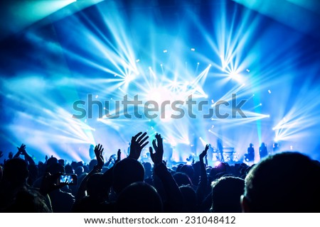 Large group of happy people enjoying rock concert, clapping with raised up hands, blue lights from the stage, new year celebration concept - stock photo