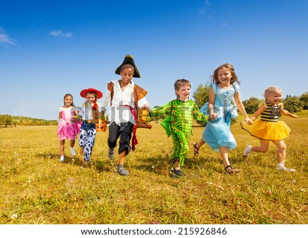 Large group of kids in Halloween costumes run  - stock photo
