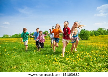 Large group of kids running in the dandelion spring field - stock photo