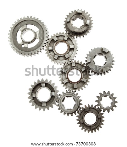 Large group of mechanical gears linked together on white - stock photo