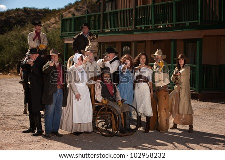 Large group of men and women in old west theme with guns - stock photo