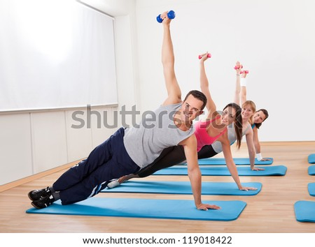 Large group of people working out in a gym balanced on one hand on their mats while raising their other arm with a dumbbell