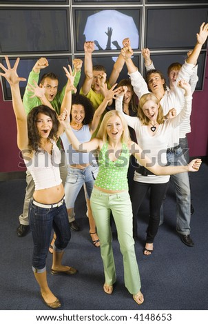 Large group of teenagers during the party. Looking at camera and holding hands up! Screaming and dancing - stock photo