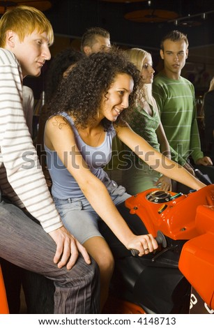 Large group of teenagers in amusement arcade. One teenage girl sitting on motorcycle. Rest of people are standing and smiling behind her - stock photo