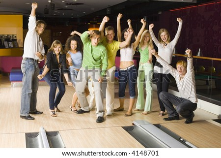 Large group of teenagers standing and cheering in bowling alley. One person crouching. Some of them are looking at camera - stock photo
