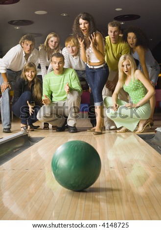 Large group of teenagers standing and crouching in bowling alley with hopeless faces. Looking at rolling ball - stock photo