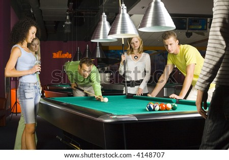 Large group of teenagers standing at pool table. Smiling and looking at balls. One person is playing billard - stock photo