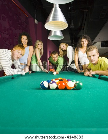Large group of teenagers standing at pool table. Smiling and looking at camera. One person is playing billard - stock photo