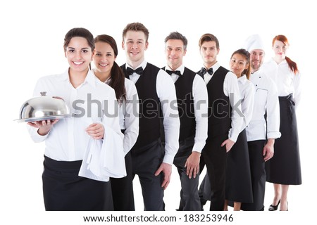 Large group of waiters and waitresses standing in row. Isolated on white - stock photo