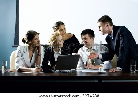 Large group of young businessman gathered together around the laptop discussing interesting question - stock photo