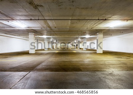 Large grungy empty undercover parking area viewed down the length with receding perspective lit by overhead strip lights