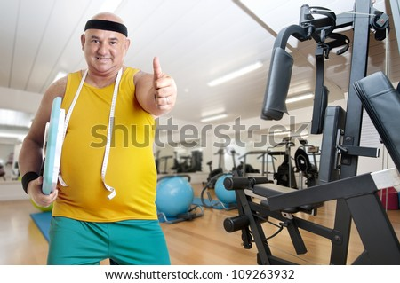 Large happy fitness man with weight scale in a gym - stock photo