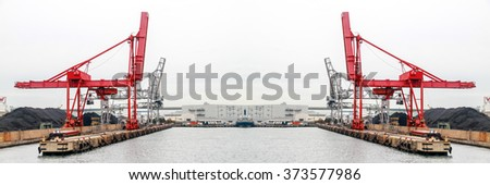 Large harbor cranes for loading and unloading coal at port - stock photo