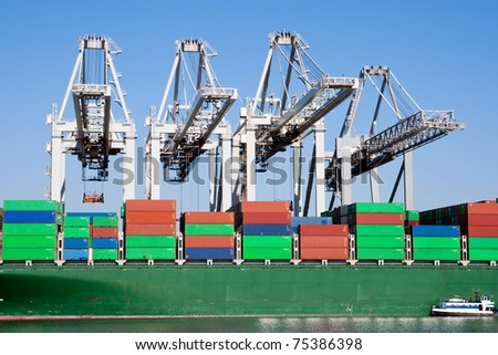 Large harbor cranes loading a container ship - stock photo