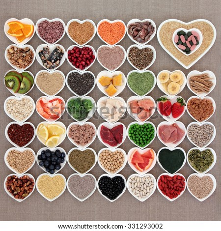 Large health and body building high protein super food in heart shaped bowls with meat, fish, pulses, cereals, grains, seeds, supplement powders, vitamin pills, fruit and vegetables. - stock photo