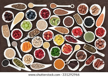 Large health and superfood collection in porcelain dishes over lokta paper background. High in minerals, vitamins and antioxidants.  - stock photo