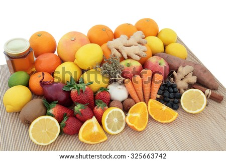 Large health food selection for cold and flu remedy with foods high in antioxidants and vitamin c on bamboo over white background. - stock photo