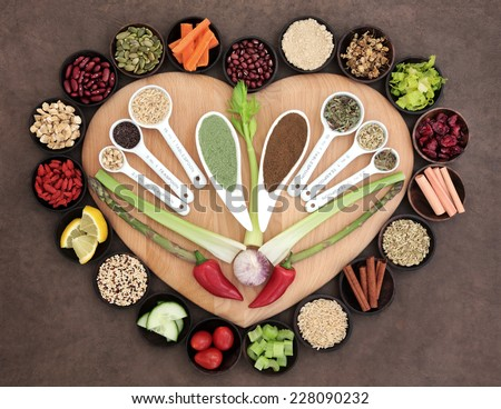 Large healthy heart superfood selection in wooden bowls and measuring spoons over brown paper background. - stock photo