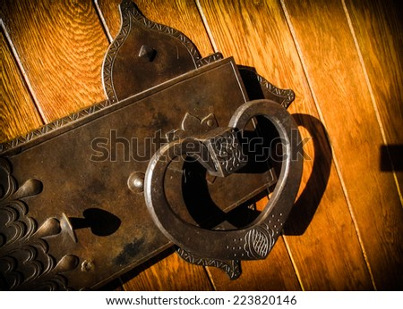 Large heart shaped antique solid brass door handle on wooden door. - stock photo