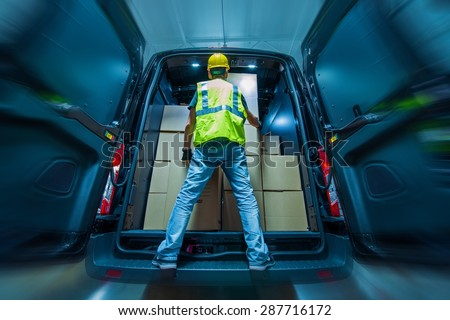Large Heavy Duty Cargo Van Loading by Men in Yellow Helmet. Shipping and Logistics Theme. - stock photo