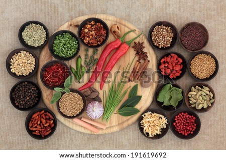 Large herb and spice selection on a wooden board, in bowls and loose. - stock photo