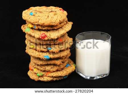 Large home made cookies and milk with black background