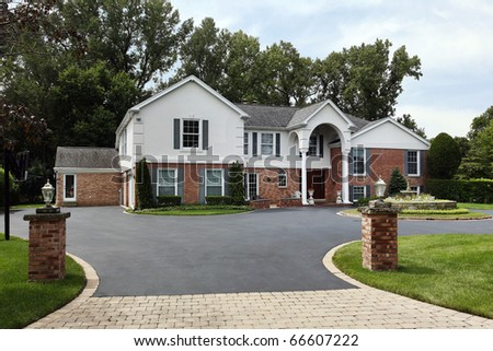 Large home with front columns and brick pillars - stock photo