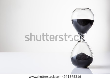 large hour glass sand timer with a lot of sand in it, time runs our slowly - stock photo
