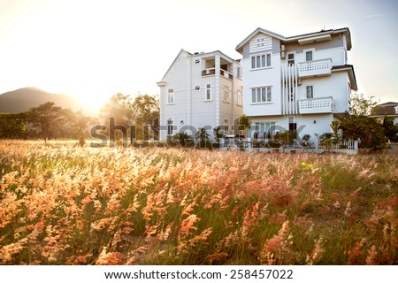 large house on a beautiful field in the mountains on the sunset, card - stock photo