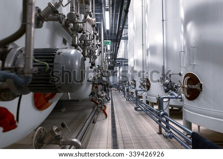 Large industrial white silos in modern factory interior - stock photo