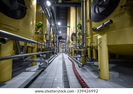 Large industrial yellow silos in modern factory interior - stock photo