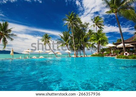 Large infinity swimming pool on the beach with palm trees - stock photo