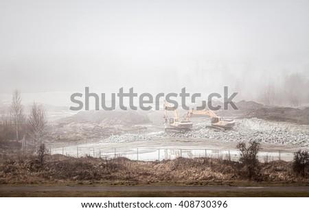 Large jackhammers smashing rocks in heavy fog. Vintage stylized photo - stock photo