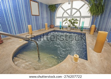 Large jacuzzi pool in room of luxury health spa center with candles - stock photo