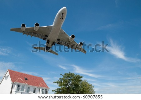 large jet aircraft on  landing approach over suburban housing - stock photo