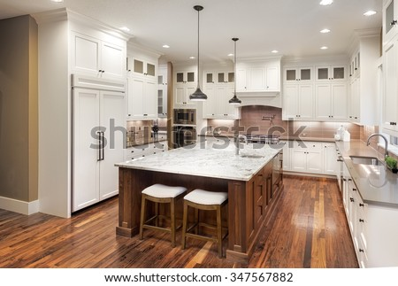 Large Kitchen Interior with Island, Sink, White Cabinets, Pendant Lights, and Hardwood Floors in New Luxury Home - stock photo