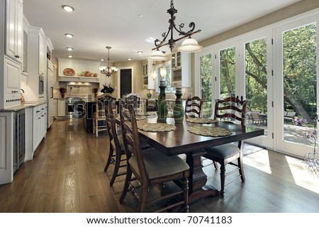 Large kitchen with white cabinetry and eating area - stock photo