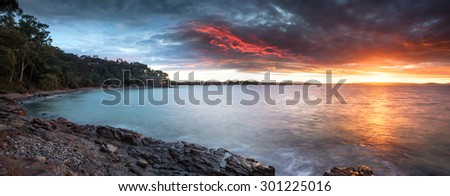 Large Landscape Panorama of a Dramatic Rocky Coastline During A Colorful Sunset Overlooking Noosa Heads, Little Cove, Sunshine Coast, Queensland, Australia - stock photo
