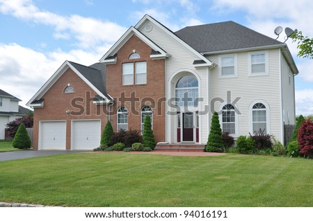 Large  Landscaped Two Car Garage Luxury Suburban Home in Residential District - stock photo
