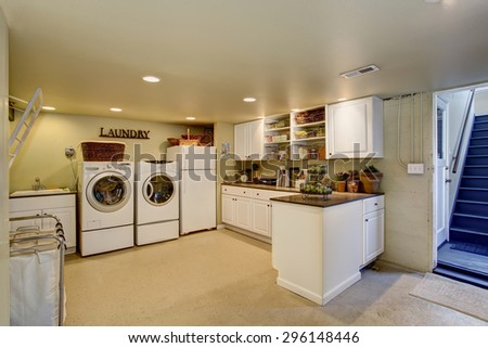 Large laundry room with appliances and white cabinets.
