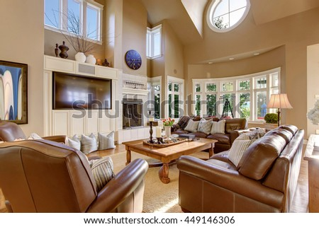 Large living room interior design with high vaulted ceiling and leather sofa set. Decorated with candles and tulips on coffee table