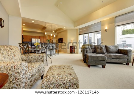 Large living room with dining table, kitchen, sofa and arm chair. - stock photo