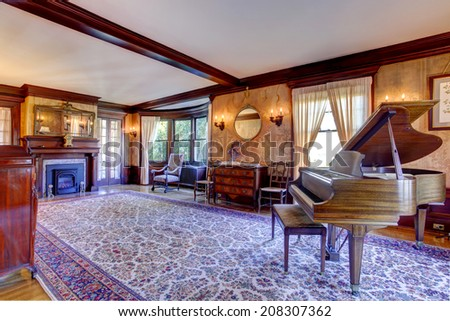 Large living room with fireplace, antique furniture and grand piano in luxury house - stock photo