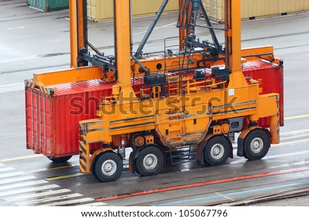Large loader drives on wet asphalt and carries red container - stock photo