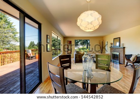 Large long living room with dining room table, balcony and fireplace. - stock photo