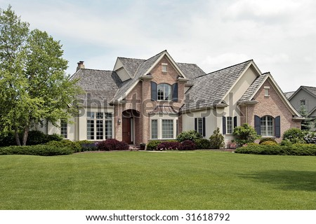 Large luxury brick home in suburban setting - stock photo