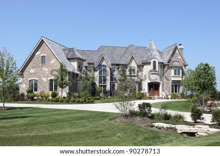 Large luxury brick home with stone turret - stock photo